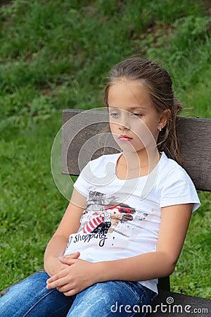 Trauriges kleines Mädchen denkt unten schauen, auf Bank
