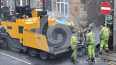 Travailleurs de route réparant la couche de surface banque de vidéos