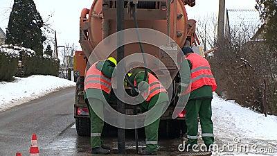 Travailleurs qualifiés à l'aide de l'équipement spécial pour pomper le drainage de résidus de la rue bien banque de vidéos