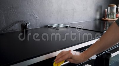 Travaux ménagers, nettoyage de la cuisine essuyer le comptoir noir et la surface de cuisson des miettes, banque de vidéos
