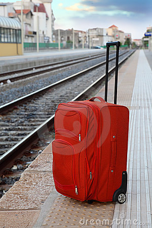 Travel bag stands on platform near railway tracks