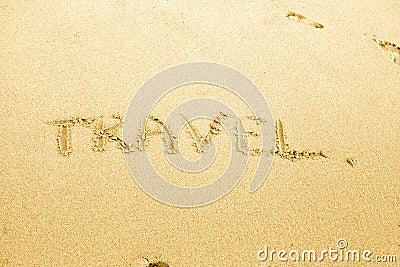 Travel text written on sand