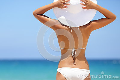 Travel woman on beach enjoying blue sea and sky