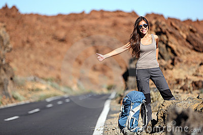 Travel woman hitchhiking on road trip
