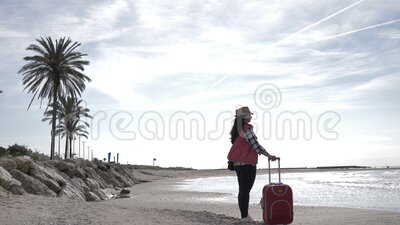 Travel woman with a suitcase stands on the coastline near the sea, travel concept, copy space. Woman tourist with a suitcase stands on the coastline near the sea stock footage