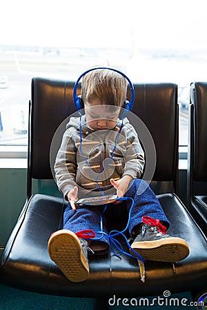 Traveler Boy Watching Movie on Phone Editorial Stock Photo