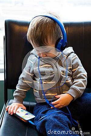 Traveler Boy Watching Movie on Phone Editorial Image