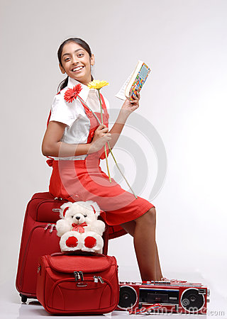 Traveler girl sitting on her luggage with a book