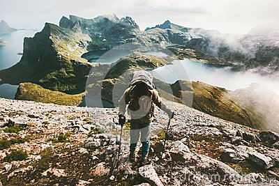 Traveler man climbing to Hermannsdalstinden mountain top in Norway Stock Photo