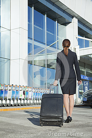 Traveler pulling suitcase into airport