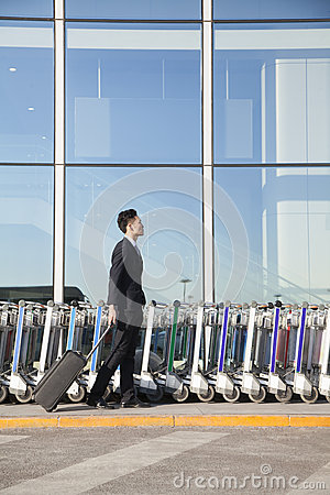 Traveler with suitcase next to row of luggage carts at airport