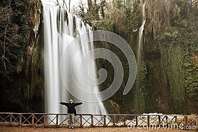 Traveler under waterfall