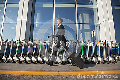 Traveler walking fast next to row of luggage carts at airport