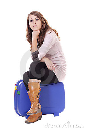 Traveling concept: woman sitting on her suitcase