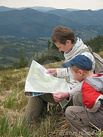 Traveling people reading map on mountains