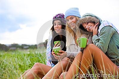 Tre amici impacchettati in su con le tazze di caffè