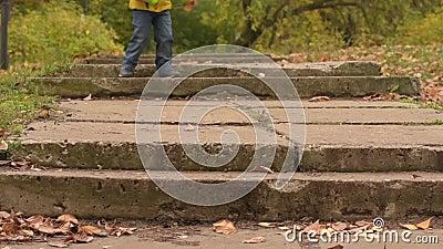 Tre anni allegri del ragazzo che ruuning le scale nel parco di autunno video d archivio