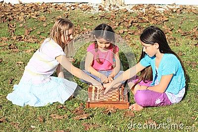 Tre flickor som spelar schack