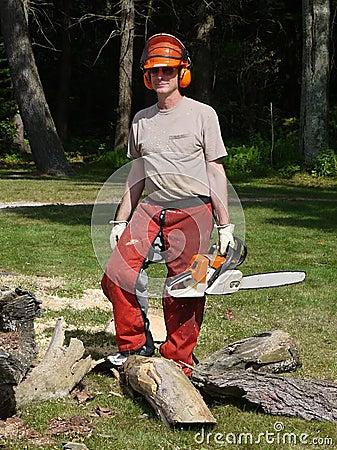 Tree felling: lumberjack man with chainsaw