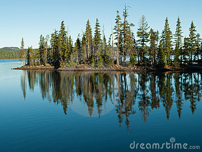 Trees reflected in still, blue lake