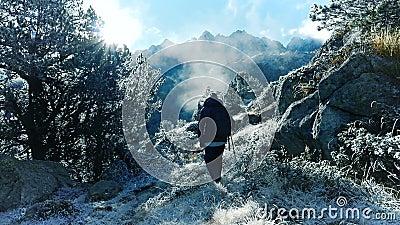 Trekking downhill in winter mountain landscape stock video