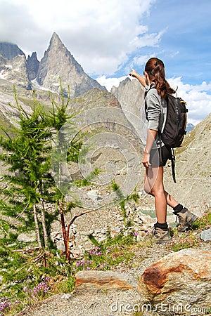 Trekking girl on high mountain trail pointing at peak