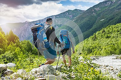 Trekking in mountains. Mountain hiking. Tourists with backpacks hike on rocky way near river. Wild nature with beautiful views. Stock Photo