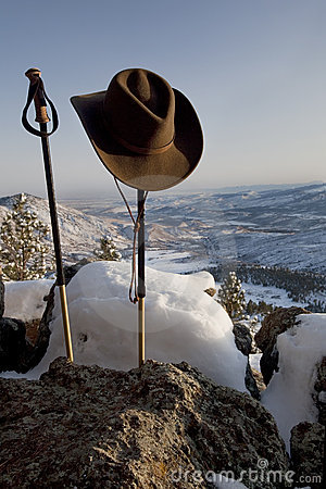 Trekking poles and hat in mountain scenery
