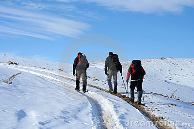 Trekking on snowy path on a sunny winter day
