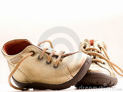 Trendy little golden baby shoes  with copyspace