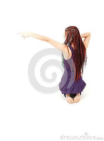 Trendy teenage girl in african plaits pointing up