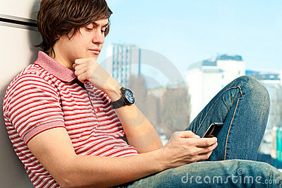 Trendy young guy typing a message