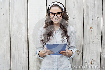 Trendy young woman with stylish glasses using tablet pc