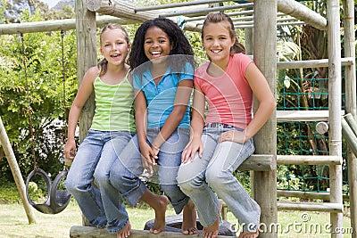 Tres amigos de la chica joven en una sonrisa del patio