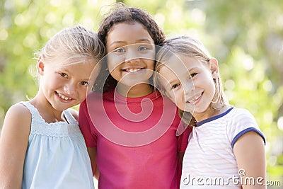 Tres amigos de la chica joven que se colocan al aire libre sonrientes