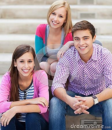 Tres amigos jovenes que se sientan junto