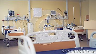 Tres camas rodadas se están mostrando en un cuarto de hospital moderno almacen de metraje de vídeo