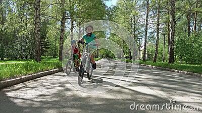 Tres hermanos que montan las bicis en día soleado almacen de video