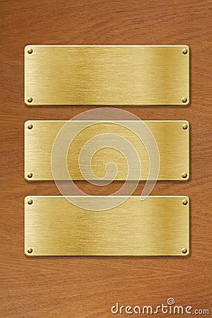 Tres placas de metal de oro sobre el fondo de madera de la textura