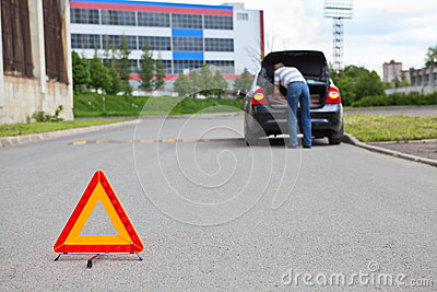 Triangle warning sign on road with driver in car
