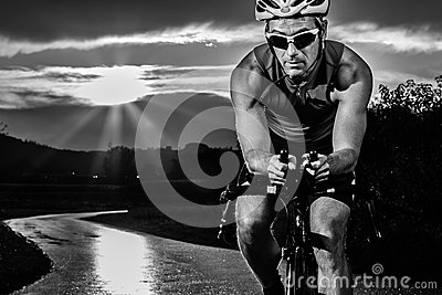 Triathlet cycling in sunrise
