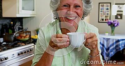 Trinkender Kaffee der glücklichen älteren Frau in der Küche 4k stock video
