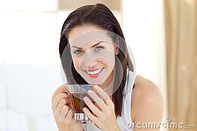 Trinkender Tee der Brunettefrau