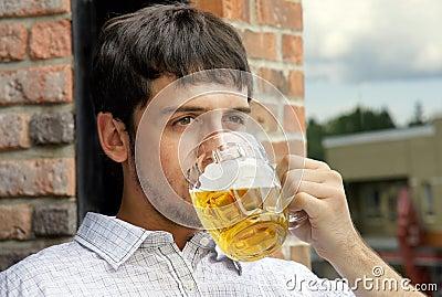 Trinkendes Bier des jungen Kerls