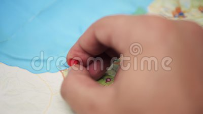 Tripod: Hand pushing a pin on to a paper map of Georgia country, Batumi. Hand pushing a pin to a paper map of Georgia country, seaside, Batumi, close up, gas stock footage