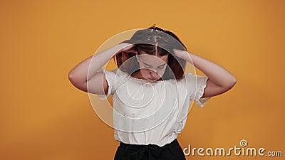 Triste femme tenant la main sur la tête, maux de tête, cheveux clignotants isolés sur le mur orange banque de vidéos