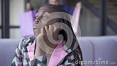 Triste mujer afroamericana sentada en el sofá de su casa mirando lejos. Hombre guapo en el traje de vuelta a casa de la tienda co almacen de metraje de vídeo