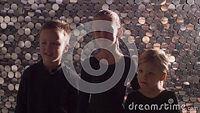 Trois enfants en vêtements noirs debout dans le Studio banque de vidéos
