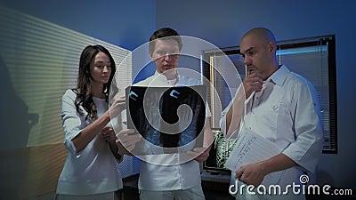 Trois médecins regardent ensemble une photo à rayons X d'un patient clips vidéos