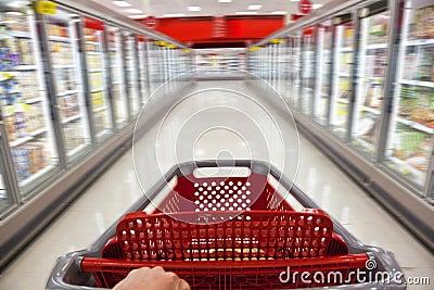 Trole da compra do borrão de movimento no supermercado